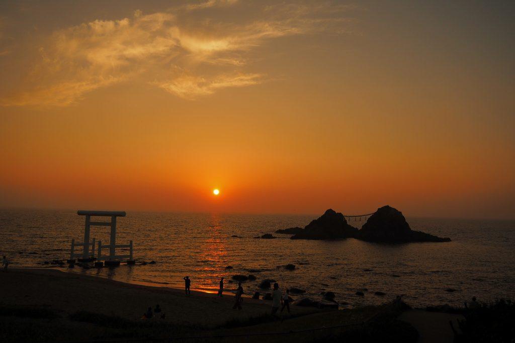 鳥居と夫婦岩の間に沈む夕日
