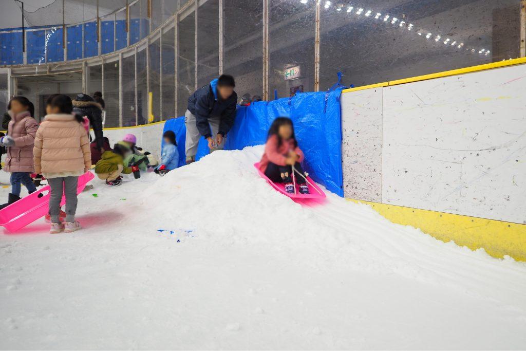 雪遊びコーナーでソリ